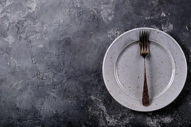 저녁 식사 장소 설정. 어두운 질감 표면에 실버 포크와 블루 현대 세라믹 플레이트. 평면도, 평면 누워.