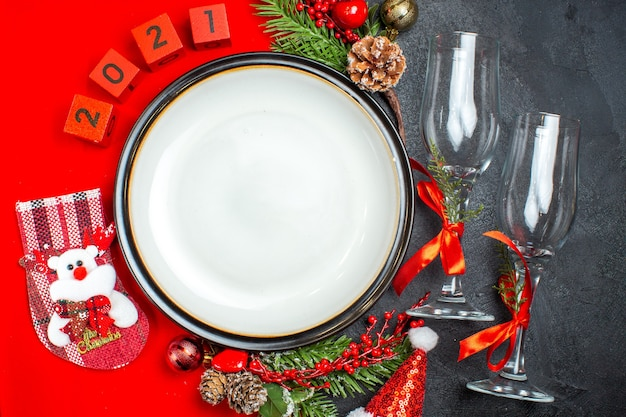 Dinner plates decoration accessories fir branches xsmas sock numbers on a red napkin and glass goblets on dark table