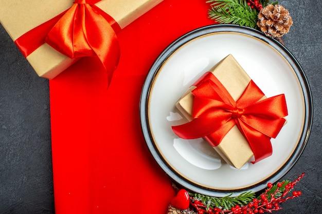 Обеденные тарелки с подарком и еловые ветки с украшением хвойной шишкой на красной салфетке