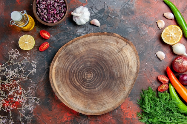 Preparazione della cena bottiglia di olio di fagioli limone e un mazzo di verde sulla tavola di colori misti