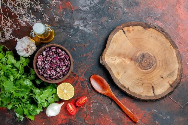 混合色のテーブルに食べ物と木製トレイ豆オイルボトルと緑の束で夕食の準備