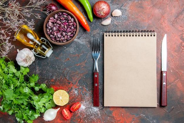 混合色のテーブルに食べ物と豆のオイルボトルとグリーンレモントマトとノートの束を使った夕食の準備