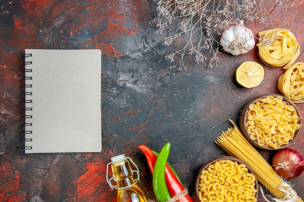 Приготовление ужина с сырыми пастами кайенский перец, связанный друг с другом веревкой, масло, бутылка, лимон, чеснок, и блокнот, на столе смешанных цветов