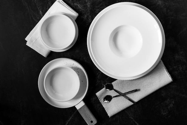 Dinner set on a dark , empty white plate with  fork and spoon