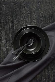 同じ色の石の背景、コピースペースにスプーンとフォークとテキスタイルタオルまたはナプキンを添えた異なるセラミックプレートの黒い色からのディナーセット。上面図。