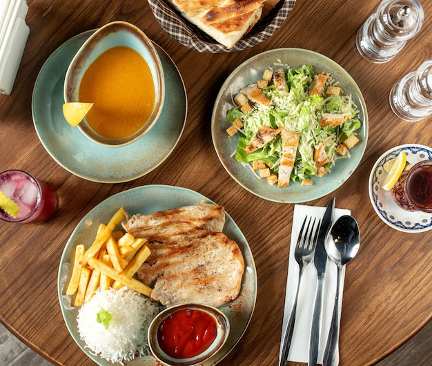 Dinner set with caesar salad, lentil soup and chicken steak served with rice and french fries