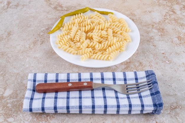 Preparazione della cena con maccheroni e forchetta su un asciugamano sulla superficie di marmo