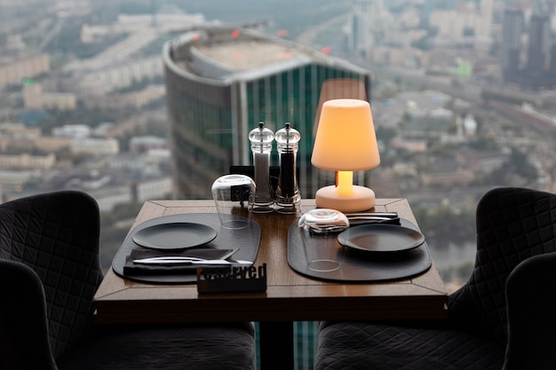 Dinner at sunset with panoramic views of the moscow business center. dinner on the background of the city. restaurant overlooking downtown. romantic setting, moscow, russia