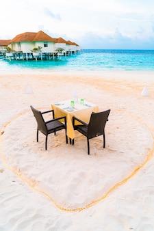 Обеденный стол и стул на пляже с фоном с видом на море на мальдивах