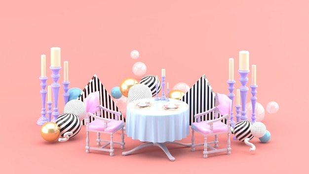 Dinner table and candle holder among colorful balls on pink space
