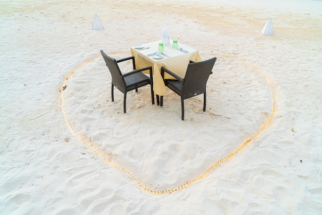 Dinner table and chair on beach with sea view background in maldives