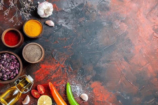 Tavolo da pranzo caduti fagioli bottiglia di olio e spezie diverse sulla tabella dei colori della miscela