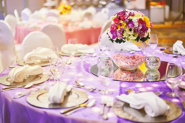 Dinner table setting with a glass vase of flower bouquet decoration