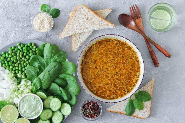 石の背景においしいスープとヘルシーなグリーンサラダのディナーテーブルトップビュー