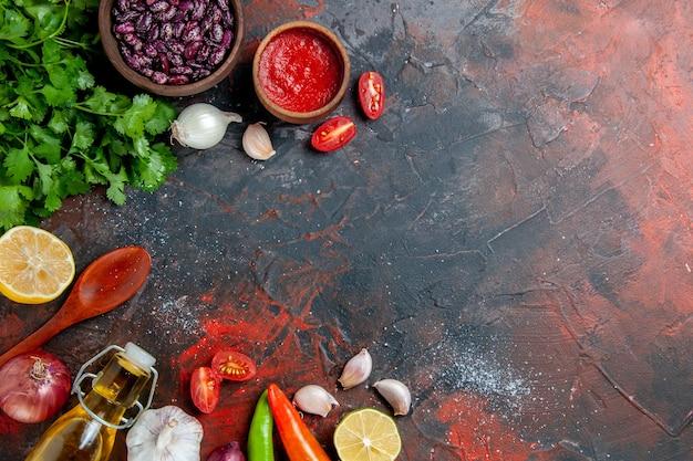 混合色のテーブルに緑のオイルボトルニンニク豆スプーンの束とディナーテーブル