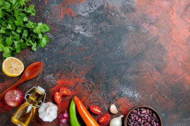 Tavolo da pranzo con un mazzo di aglio bottiglia di olio verde e cucchiaio sul tavolo di colori misti