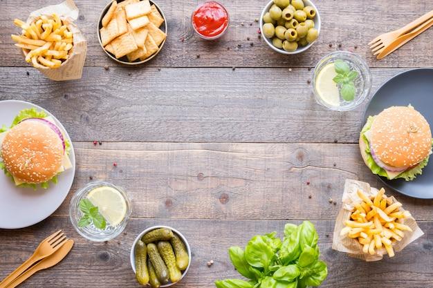 Обеденный стол с гамбургерами, картофелем фри, овощами, соусами, закусками и лимонадом