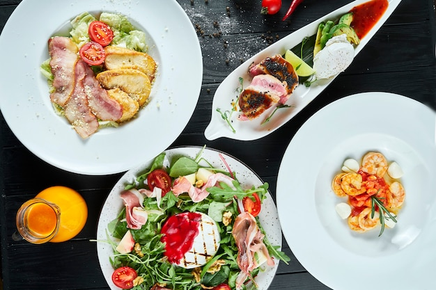 Dinner table with different dishes - caesar salad, tuna steak, shrimp soup, grilled camembert salad