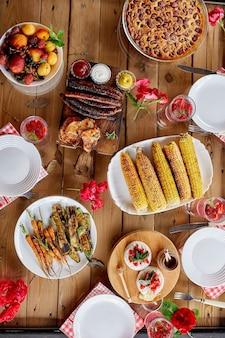 肉グリル、ソーセージ、トウモロコシ、ロースト野菜、ソース、スナック、レモネード、上面図、家族の夕食または昼食、食事の概念を備えたディナーテーブル