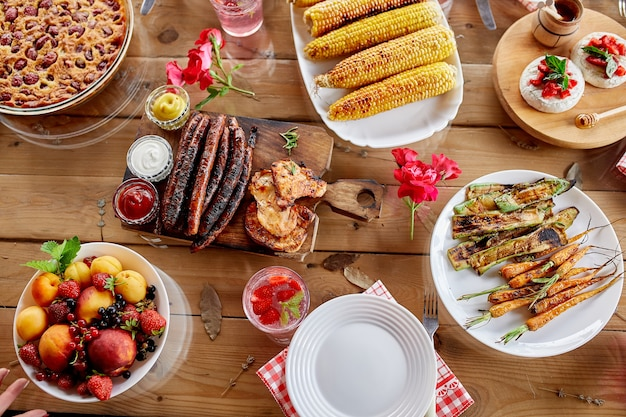 Обеденный стол с мясным грилем, сосисками, кукурузой, жареными овощами, соусами, закусками и лимонадом.