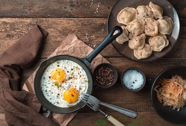 Обеденный стол с яичницей, пельменями и капустой. вид сверху. понятие о кулинарных традициях.