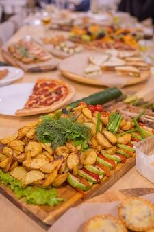 美しい夏の花で飾られた軽食付きのディナーテーブルフードテーブル健康的なおいしい臓器...