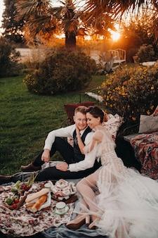 ピクニックでブライダルカップルと夕食をとります。カップルはフランスで日没時にリラックスしています。プロヴァンスでのピクニックで新郎新婦。