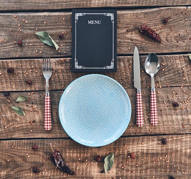 Время ужина. выстрел под большим углом: пустая тарелка, вилка, ложка, нож и закрытое меню
