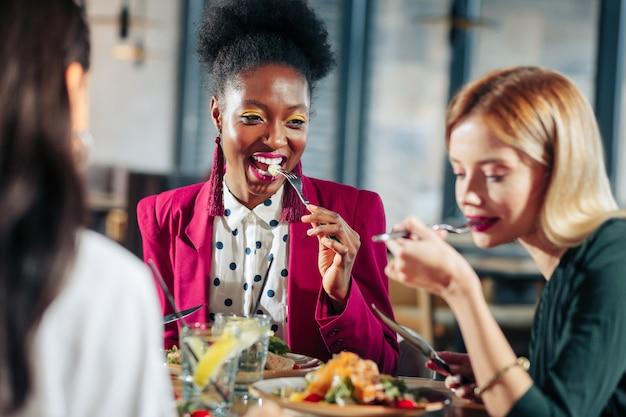 Ужин вместе три стильные привлекательные женщины вместе вкусно поужинают в хорошем ресторане