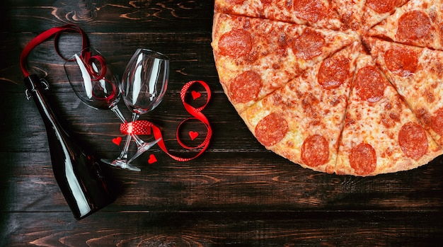 Dinner for two in honor of valentine's day with pizza and wine.