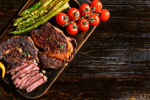 Dinner for two juicy delicious steaks, asparagus with parmesan and vegetables.