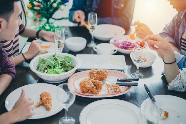 Ужин с азиатской группой лучших друзей, наслаждающихся вечерними напитками, сидя вместе за обеденным столом на кухне