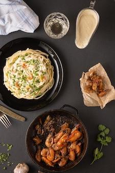 Ужин с жареными креветками и пастой в белом соусе.