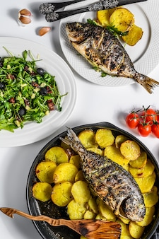 Dinner with grilled sea bream fish, arugula salad with tomatoes, baked potatoes. white background. top view
