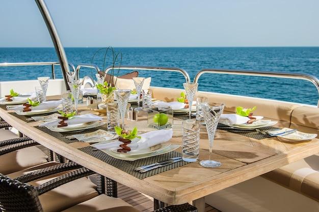 Обеденный стол на верхней палубе роскошной яхты