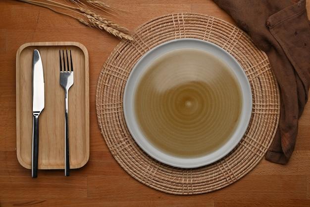モックアップセラミックプレートカトラリーランチョンマットとナプキンを備えたダイニングテーブル