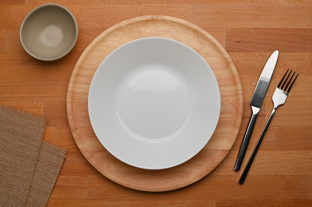 Dinning table with mock up ceramic plate cutlery and place mat