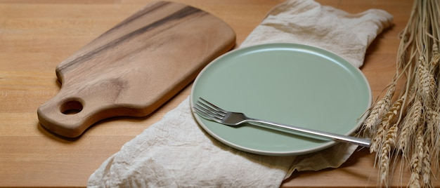 Dinning table with mock-up wooden tray, ceramic plate, silver fork on napkin and decoration