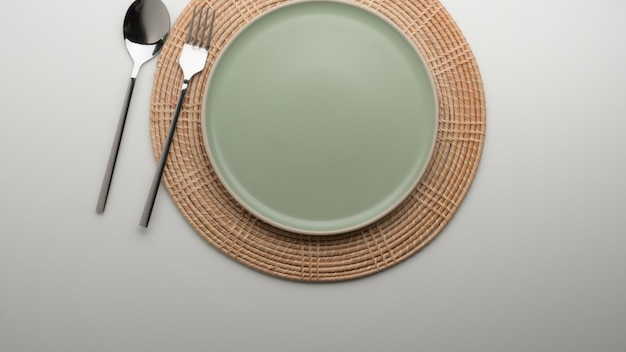 Dinning table with  turquoise ceramic plate and silverware on placemat