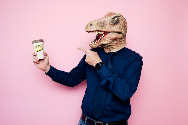 Dinosaur-headed man pointing at a recyclable cardboard coffee cups.