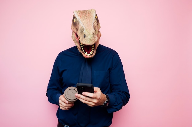 Dinosaur-headed man with a cup of coffee and a smartphone.
