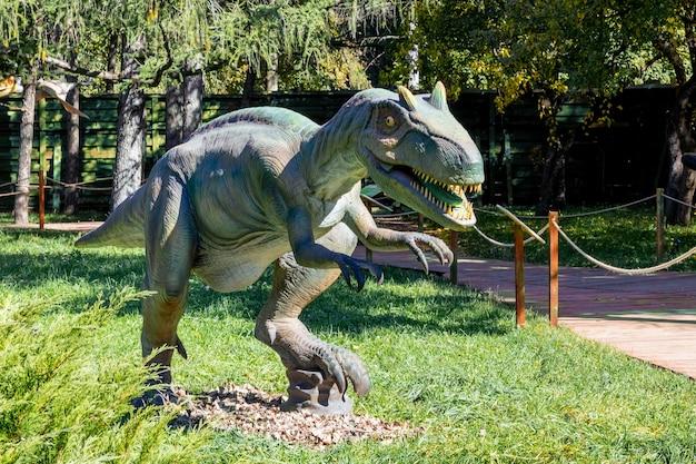 公園の恐竜モデル。夏の晴れた日の公園での展示会での巨大メガラプトル