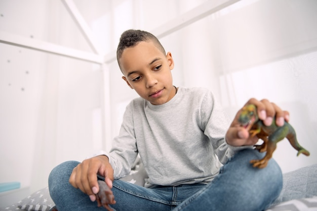 Dinosaur toy. pretty afro american boy looking down while holding dinosaurs toys