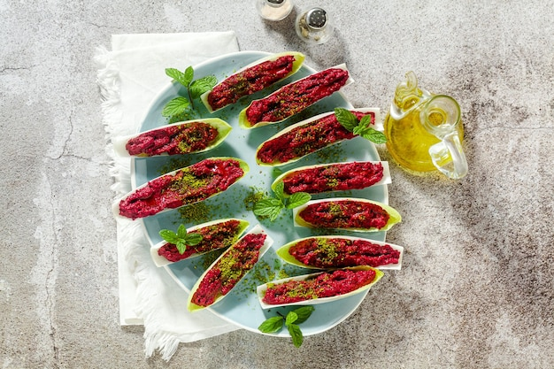 Dip of boiled beets and pistachios in leaves of belgian endive with mint. healthy summer snack