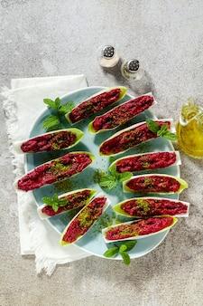 Обвалять вареную свеклу и фисташки в листьях бельгийского эндивия с мятой. здоровая летняя закуска