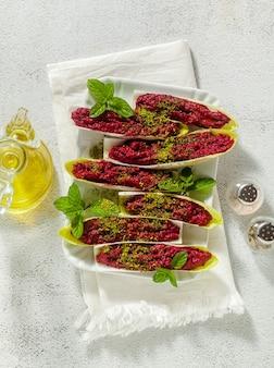 ミントとベルギーエンダイブの葉に茹でたビートとピスタチオのディップ。ヘルシーな夏のおやつ