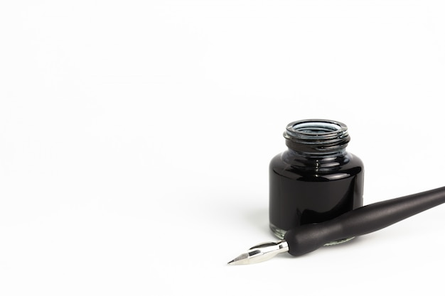 Dip pen and bottle of ink on isolated white background