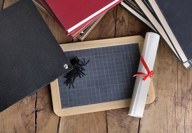 Diploma with a chalkboard and graduation hat on a wooden table