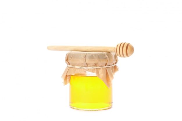Ковш и стеклянная банка с медом, изолированные на белом