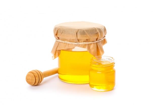 Ковш и стеклянные банки с медом, изолированные на белом